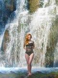 Bella ragazza che posa in un'alta cascata, ragazza assolutamente abbandonata della testarossa in una cascata Immagine Stock