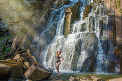 Bella ragazza che posa in un'alta cascata, ragazza assolutamente abbandonata della testarossa in una cascata Fotografie Stock