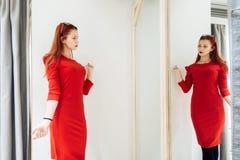 Bella ragazza che prova su un vestito rosso nel deposito Donna graziosa che posa vicino al capriccio immagini stock