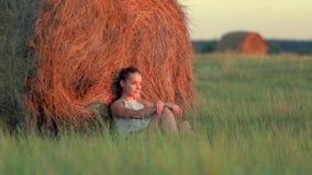 Bella ragazza che riposa alle pile di fieno al tramonto stock footage