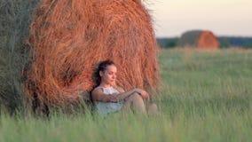 Bella ragazza che riposa alle pile di fieno al tramonto video d archivio