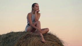Bella ragazza che riposa alle pile di fieno al tramonto archivi video