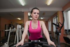 Bella ragazza che si esercita in un club di forma fisica su una bici fissa Immagini Stock Libere da Diritti