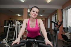 Bella ragazza che si esercita in un club di forma fisica su una bici fissa Fotografia Stock Libera da Diritti