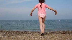 Bella ragazza che si imbatte nel mare al tramonto archivi video