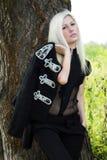 Bella ragazza che si leva in piedi vicino ad un albero Immagine Stock Libera da Diritti