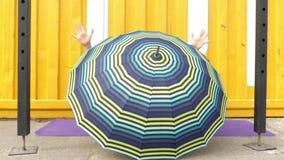Bella ragazza che si nasconde dietro un ombrello stock footage
