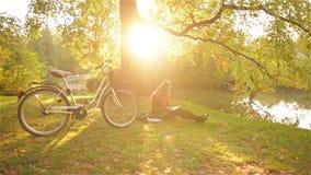 Bella ragazza che si rilassa in libro di lettura del parco di autunno, seduta sull'erba vicino al lago con la sua bicicletta Gior stock footage