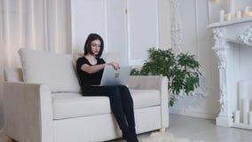 Bella ragazza che si rilassa sul sofà facendo uso del computer portatile video d archivio