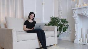 Bella ragazza che si rilassa sul sofà facendo uso del computer portatile e che smilling stock footage