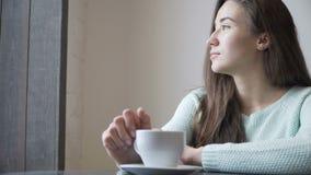 Bella ragazza che si siede ad una tavola e ad un tè bevente Distensione stock footage