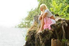 Bella ragazza che si siede al puntello e che osserva via immagine stock