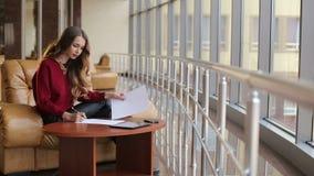 Bella ragazza che si siede alla tavola con i documenti in una costruzione moderna archivi video