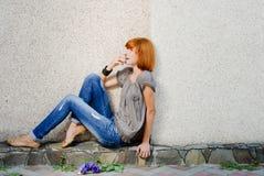 Bella ragazza che si siede contro la parete e che osserva in su Fotografie Stock