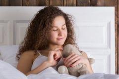Bella ragazza che si siede a letto e che abbraccia giocattolo molle Fotografia Stock