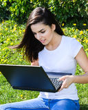 Bella ragazza che si siede nel parco con un computer portatile fotografia stock