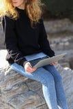 Bella ragazza che si siede nel parco con un computer portatile e che parla su Internet Immagine Stock Libera da Diritti