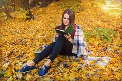 Bella ragazza che si siede nella foresta di autunno, in plaid che legge un libro Foto accogliente del modello di autunno in fogli Immagini Stock