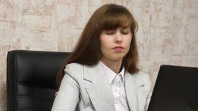 Bella ragazza che si siede nella sedia in ufficio e che scrive sul computer portatile donna di affari della giovane donna che lav stock footage