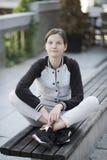 Bella ragazza che si siede su un banco Fotografia Stock