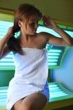 Bella ragazza che si siede su un solarium Immagini Stock