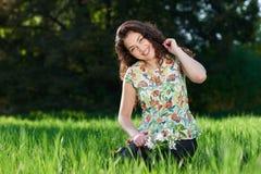 Bella ragazza che si siede su una radura nel parco, nel sole luminoso e nelle ombre sull'erba fotografia stock