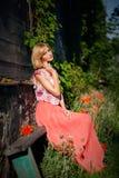 Bella ragazza che si siede sul banco fotografie stock libere da diritti