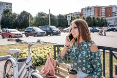 Bella ragazza che si siede sul banco, sulla bici e sulla borsa di estate su aria fresca Stile di vita in citt? Chiamate sul telef fotografie stock