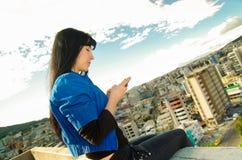 Bella ragazza che si siede sul tetto facendo uso di lei Immagini Stock Libere da Diritti