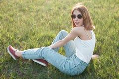 Bella ragazza che si siede sull'erba Fotografie Stock Libere da Diritti