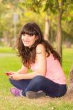 Bella ragazza che si siede sull'erba in parco Fotografia Stock