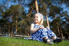 Bella ragazza che si siede sull'erba verde fotografia stock libera da diritti