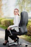 Bella ragazza che si siede sulla presidenza Fotografia Stock