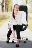 Bella ragazza che si siede sulla presidenza Fotografie Stock