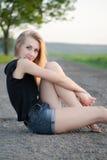 Bella ragazza che si siede sulla strada Fotografie Stock Libere da Diritti