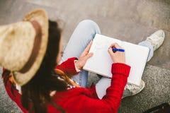 Bella ragazza che si siede sulla via con un taccuino e una penna a disposizione, facendo le note ed i resti Immagine Stock Libera da Diritti