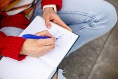 Bella ragazza che si siede sulla via con un taccuino e una penna a disposizione, facendo le note ed i resti Fotografia Stock