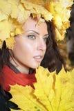 Bella ragazza che si siede sulle foglie gialle Immagini Stock Libere da Diritti
