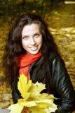 Bella ragazza che si siede sulle foglie gialle Fotografie Stock Libere da Diritti
