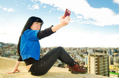 Bella ragazza che si siede sullo sguardo del tetto Fotografie Stock Libere da Diritti