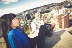 Bella ragazza che si siede sullo sguardo del tetto Fotografie Stock