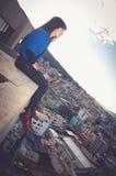 Bella ragazza che si siede sullo sguardo del tetto Immagine Stock Libera da Diritti