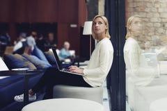 Bella ragazza che si siede in un caffè con un computer Fotografia Stock