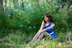 Bella ragazza che si siede in una radura della foresta Immagine Stock