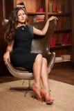 Bella ragazza che si siede in una sedia di cuoio Fotografie Stock Libere da Diritti