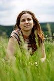 Bella ragazza che si trova giù dell'erba Immagini Stock