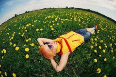 Bella ragazza che si trova su un prato in un campo dei fiori, denti di leone Immagine Stock