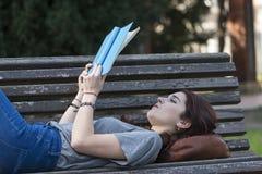 Bella ragazza che si trova sul banco e sul libro blu colto, all'aperto Immagine Stock Libera da Diritti