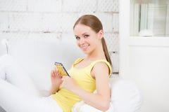 Bella ragazza che si trova sul sofà e sulla compressa commovente Fotografia Stock Libera da Diritti