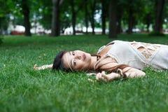 Bella ragazza che si trova sull'erba nel parco di estate Immagini Stock